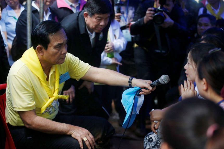 Thailand's Prime Minister Prayut Chan-o-cha holds a microphone as he listens to family members near the Tham Luang cave complex during an ongoing search for members of an under-16 soccer team and their coach on June 29, 2018.