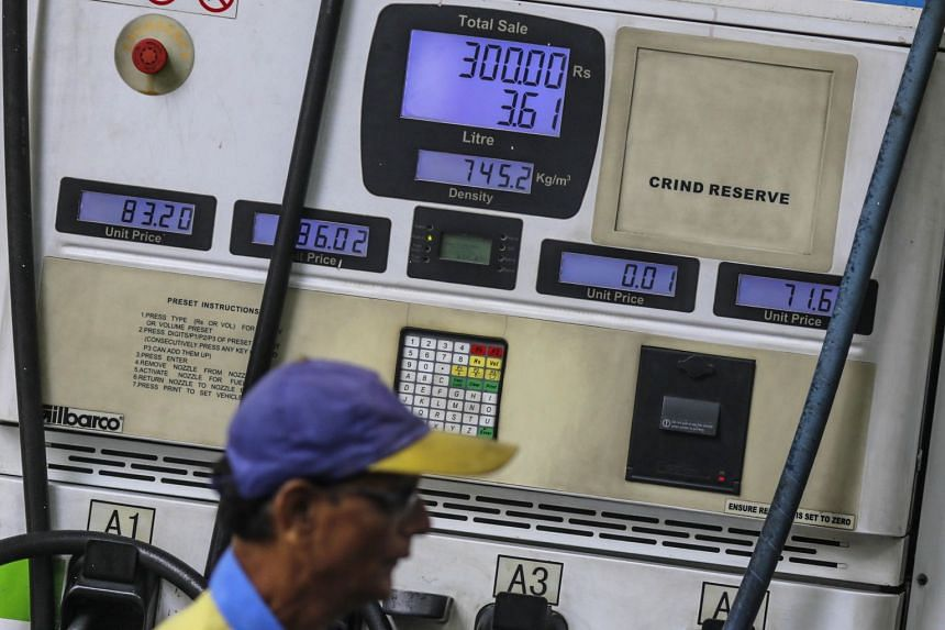 A worker walking past a petrol pump in Mumbai, India. The biggest buyer of Iranian oil after China, India will be forced to take action to protect its exposure to the US financial system.