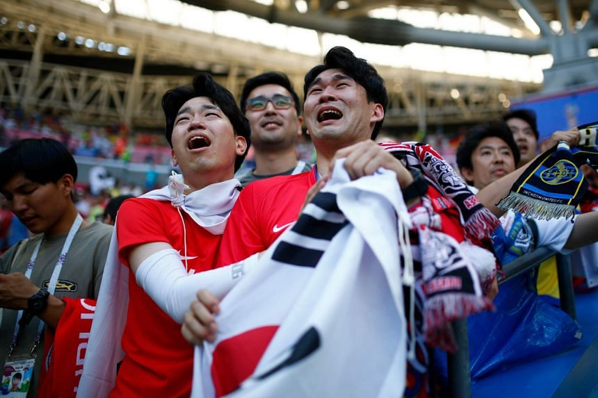South Korean supporters reacting to the manner of their bittersweet victory over Germany. The Asian nation exited the tournament despite recording their first Finals win against Die Mannschaft.