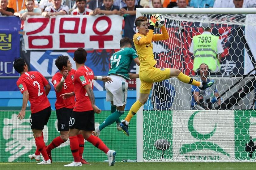 South Korea's goalkeeper Cho Hyun-woo (right) makes a save during the Russia 2018 World Cup Group F football match between South Korea and Germany at the Kazan Arena in Kazan on June 27, 2018.