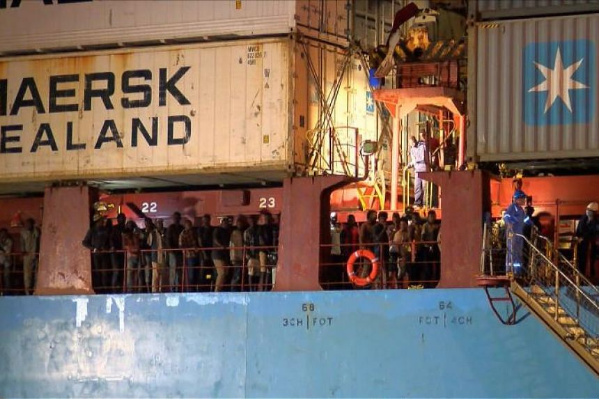 Rescued migrants are seen waiting to disembark from the Danish container ship, the Alexander Maersk, at the port of Sicilian port of Pozzallo on June 26, 2018.