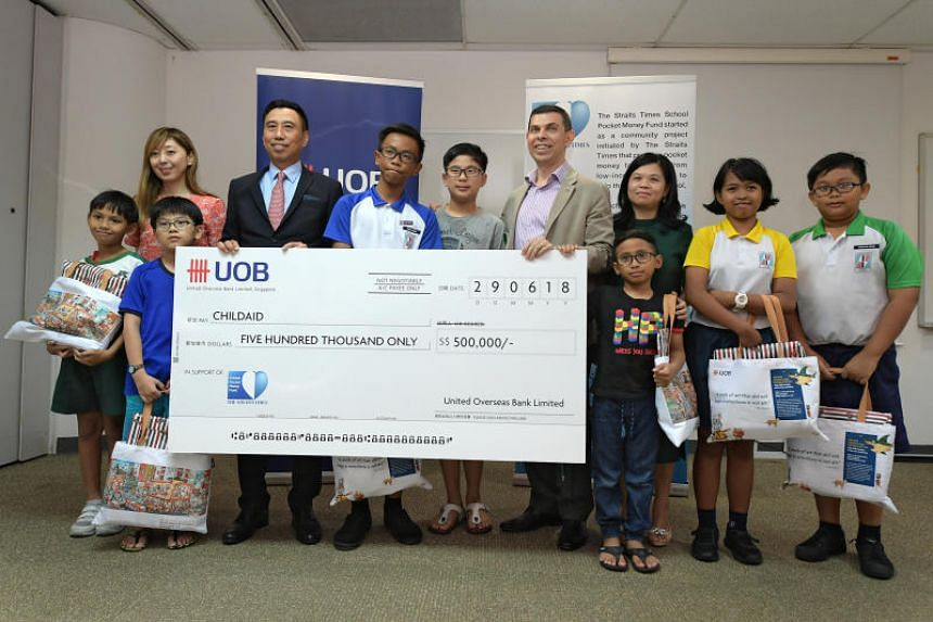 Mr Eric Tham (fourth from left), managing director and head of group commercial banking at UOB, presenting a cheque to Mr Warren Fernandez, chairman of The Straits Times School Pocket Money Fund, on June 29, 2018.
