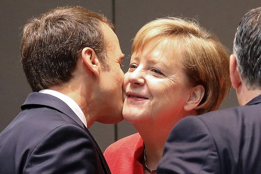 France's President Emmanuel Macron and Germany's Chancellor Angela Merkel share a light moment outside EU talks in Brussels yesterday.