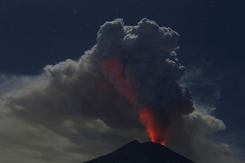 The erupting Mount Agung volcano as seen from Datah village in Bali's Karangasem regency yesterday. The volcano, which caused the evacuation of tens of thousands of people when it erupted previously late last year, hurled ash more than 2km into the s