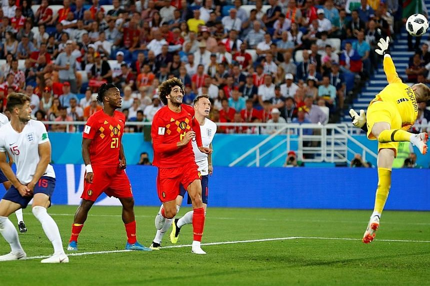 England goalkeeper Jordan Pickford diving in vain as Belgium's Adnan Januzaj (not in photo) scores the only goal in the match six minutes into the second half. Belgium will face Japan in the round of 16 on Monday, while England have Colombia to conte