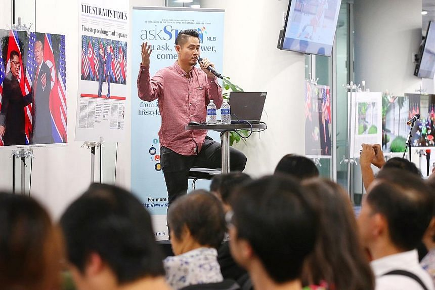 Straits Times executive photojournalist Kevin Lim speaking at the askST@NLB session yesterday at the NLB building, where his photos from the June 12 summit were on display.