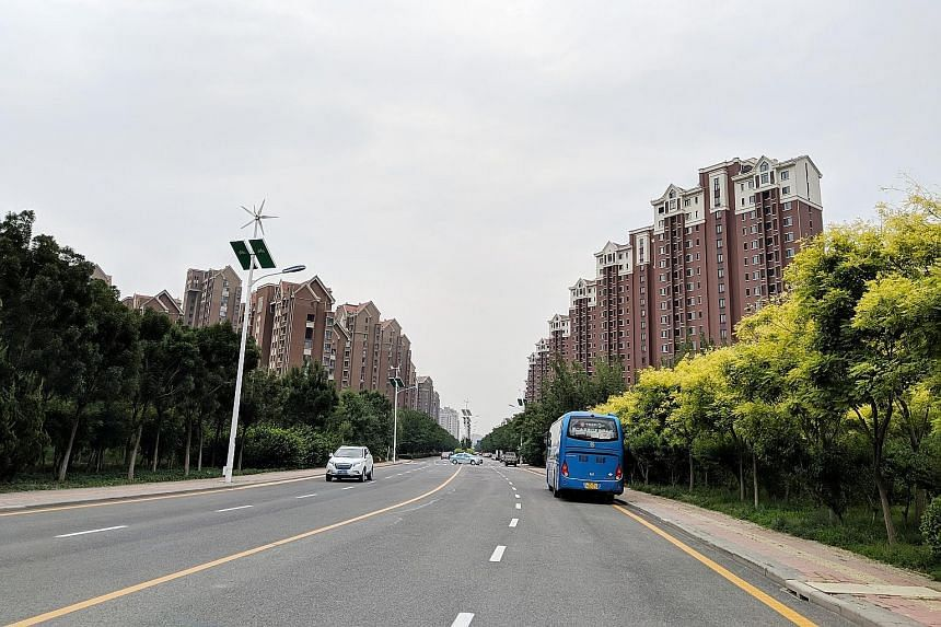 Some lampposts in the Tianjin Eco-city are equipped with wind turbines and solar panels to generate electricity. The eco-city also features housing similar to the HDB blocks seen in Singapore.