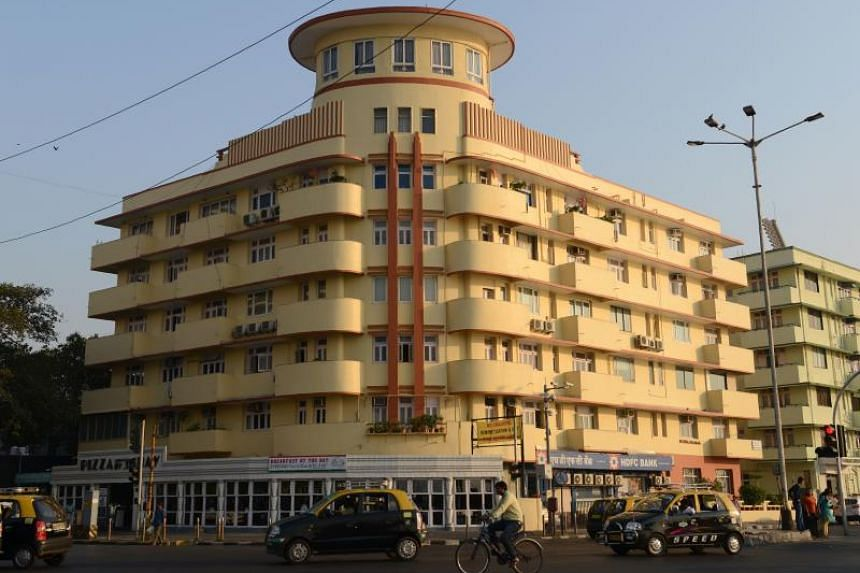 Vehicles passing by an Art Deco building on Marine Drive in Mumbai, India. The Art Deco buildings house residential properties, commercial offices, hospitals and single screen movie theatres.