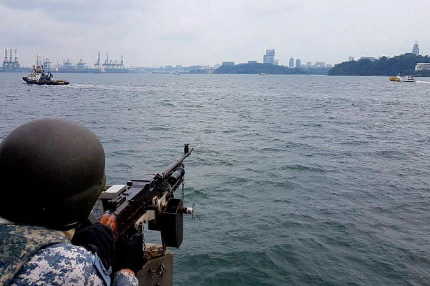 A member of the Republic of Singapore Navy keeps watch as navy ships patrol the waters around Sentosa during a summit between US President Donald Trump and North Korean leader Kim Jong Un on June 12, 2018.