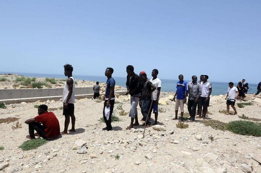Migrants who survived the sinking of an inflatable dinghy boat off of the coast of Libya arrive on the shore of al-Hmidiya, east of the capital Tripoli on June 29, 2018.
