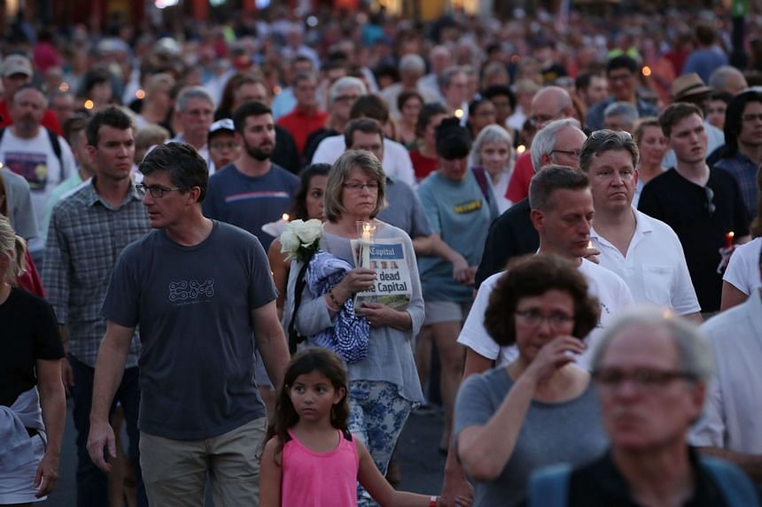 People attending a candlelight vigil to honour the 5 people who were shot and killed at the Capital Gazette newpaper office, on June 29, 2018, in Annapolis, Maryland.