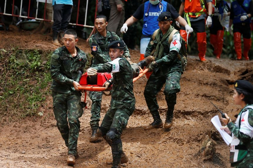 Soldiers and rescue workers carry out a simulated victim during a drill, near the Tham Luang cave complex, as an ongoing search for members of an under-16 soccer team and their coach continues.