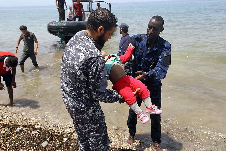 Members of the Libyan security forces carrying the body of a baby as survivors of the shipwreck off the coast of Libya were brought to shore in Al-Hmidiya, east of Tripoli, on Friday. Around 120 migrants were aboard the inflatable craft when it ran i