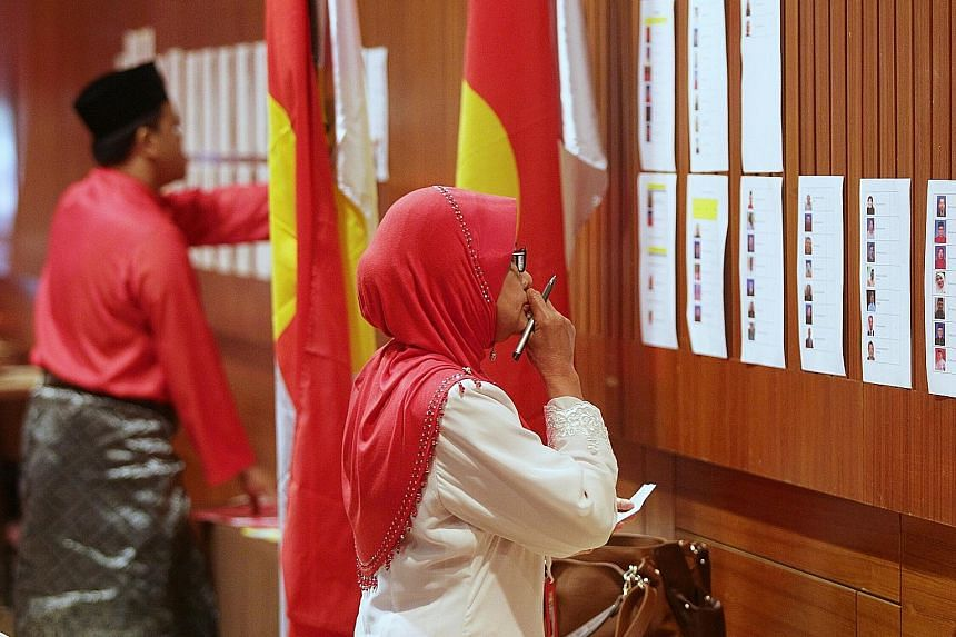 Mr Ahmad Zahid Hamidi (above) said he can return Umno to power before the next general election. (Top) Umno members viewing the candidates' pictures before casting their votes.