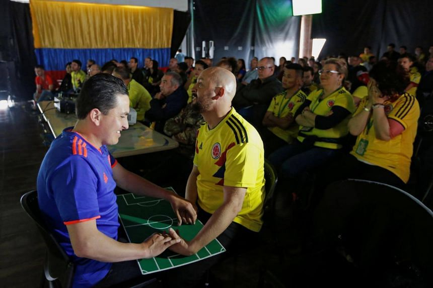 Jose Richard Gallego (left) follows the match with the help of his guide Cesar Daza.