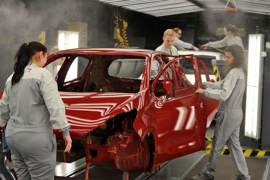 Employees work on the assembly line of the Peugeot 208 car by French carmaker PSA Peugeot Citroen at the company's automobile factory in Trnava, western Slovakia.