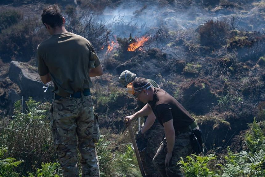 British Army soldiers help dig ditches and 'breaks' to maintain the fires as they continue to support Great Manchester Fire and Rescue Service with the Saddleworth Moor fire, north west England, Britain, on June 29, 2018.