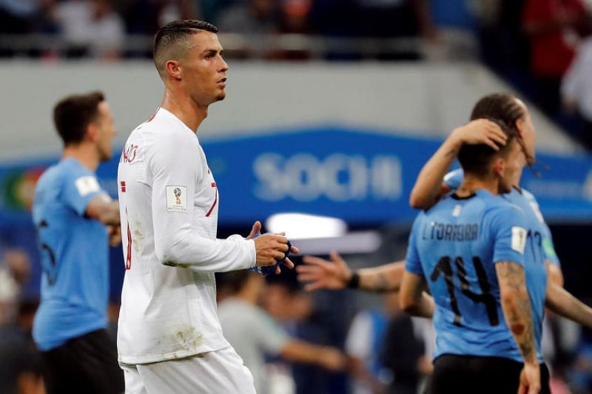 Portugal's Cristiano Ronaldo looks dejected at the end of the match as Uruguay's Lucas Torreira and Diego Laxalt celebrate.