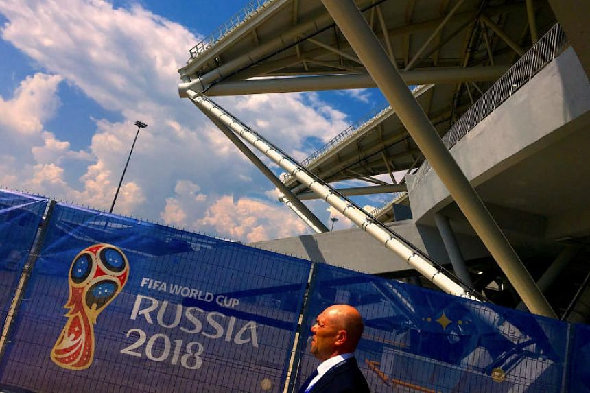 A security guard walks past a fence displaying a FIFA World Cup banner at Samara Stadium in Russia, on June 27, 2018.