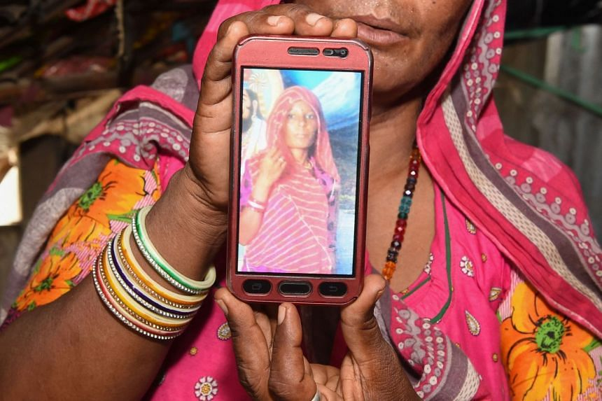 Ms Mohinidevi Nath displays a photo of her cousin Shantadevi Nath, killed by a mob that believed she was intent on abducting children.