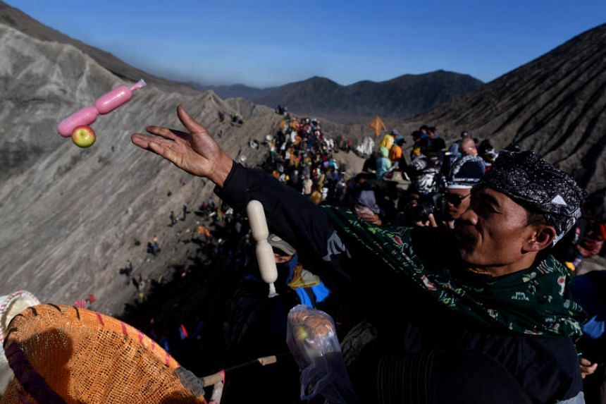 A worshipper throwing an offering into the volcanic crater of Mount Bromo during the Kasada ceremony in Probolinggo, Indonesia, on June 30, 2018.