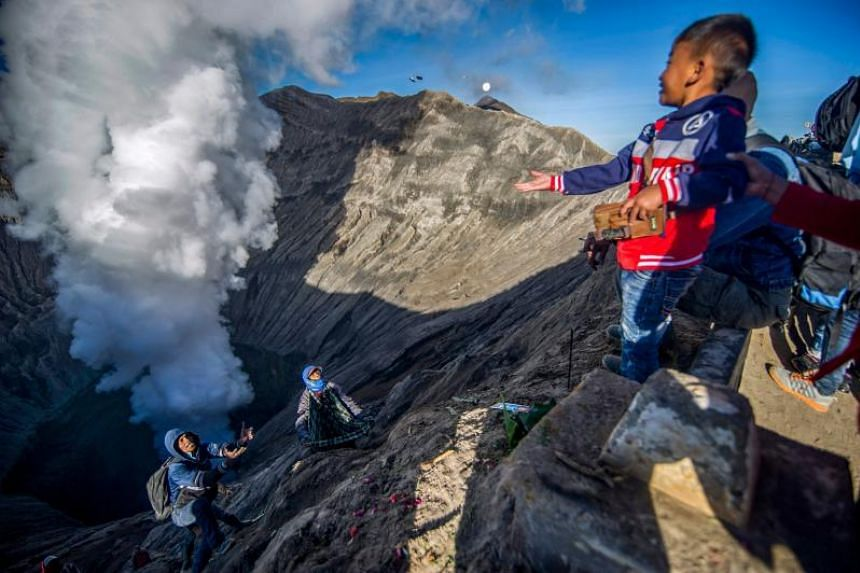 A boy from the Tengger tribe throwing coins into the crater of Mount Bromo as an offering, as part of the Yadnya Kasada festival, on June 30, 2018.