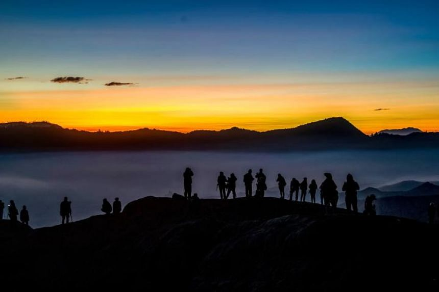 Tourists standing on the summit ridge of Mount Bromo waiting for Tengger tribespeople to deliver their offerings, on June 30, 2018.