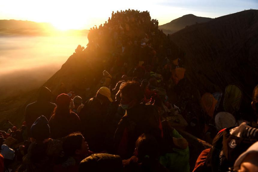 Hindu worshippers and villagers standing on the slopes the crater of Mount Bromo during the Kasada ceremony in Probolinggo, Indonesia, on June 30, 2018.