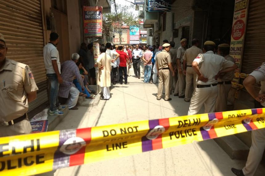 Police officers cordoning off a house where 11 members from a family were found dead, in New Delhi on July 1, 2018.