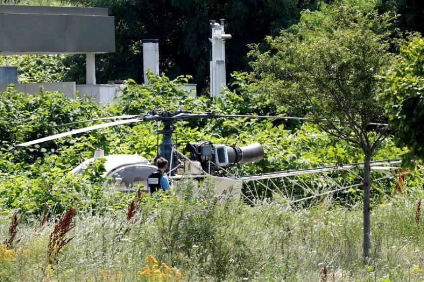A French police officer examining an abandoned Alouette II helicopter used by robber Redoine Faid to escape from prison, in Gonesse on July 1, 2018.