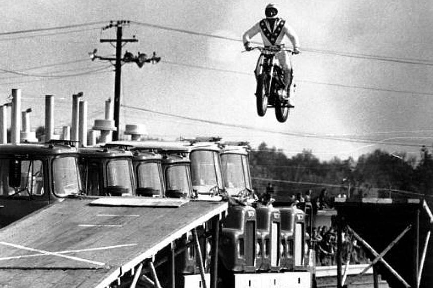 Evel Knievel jumping over 10 Mack trucks (left) at Dragway 42 in Cleveland in May 1974. The motorcycle daredevil (right) died in 2007.
