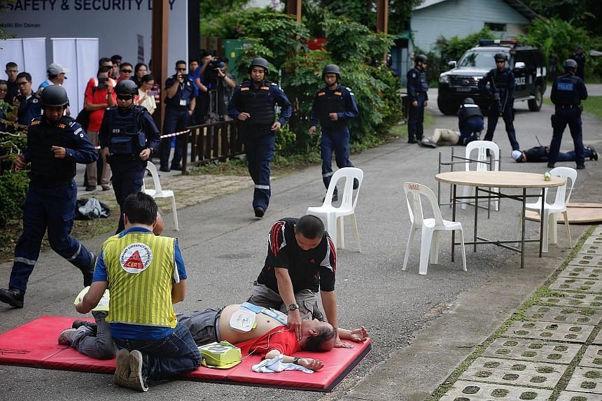 """Volunteers from the Siglap C2E Community Emergency Response Team attending to a """"victim"""" who suffered a """"heart attack"""", after """"terrorists"""" who fired into a """"coffee shop"""" (below) were apprehended during a counter-terrorism exercise on Pulau Ubin yeste"""