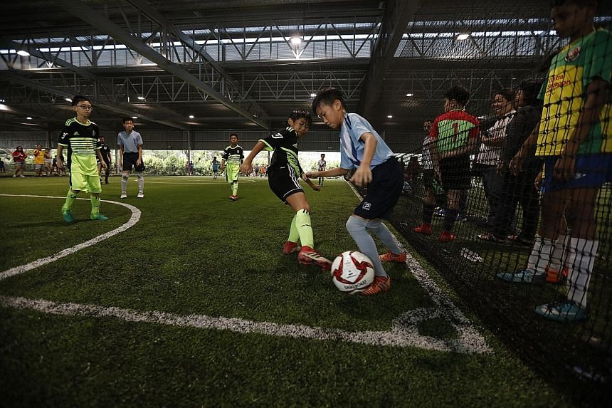 Kids playing in the Plate final of the S. Chandra Das Cup six-a-side futsal competition at the FutsalArena@Yishun yesterday. Organised by Tamil Murasu and backed by the People's Association's Narpani Pearavai or Indian Activity Executive Committees C