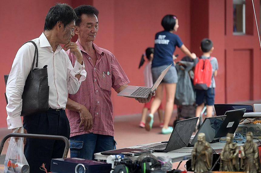 Mr Steven Low (second from left), 60, showing a laptop to a potential customer in Toa Payoh. He is among the former Sungei Road flea market vendors who have splintered across the island. Vendors hawking their wares at the Woodlands Recreation Centre,