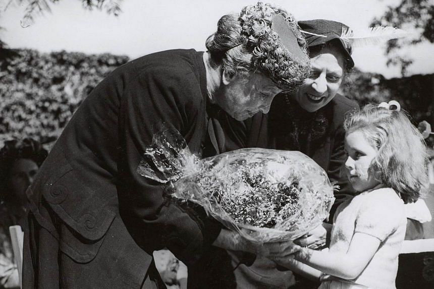 File photo showing Helen Keller receiving a bouquet from a child.