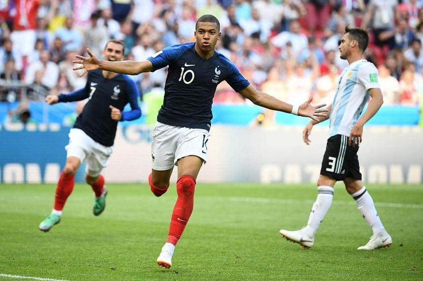 France's forward Kylian Mbappe (centre) celebrates after scoring a goal against Argentina at the Kazan Arena in Kazan, Russia, on June 30, 2018.