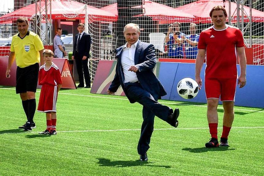 Russia's President Vladimir Putin (centre) kicks a ball as he takes part in the opening of an exhibition soccer match at the World Cup Football Park on the Red Square in Moscow on June 28, 2018.