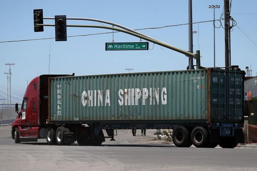 A truck carries a shipping container from China Shipping at the Port of Oakland on June 20, 2018, in California.