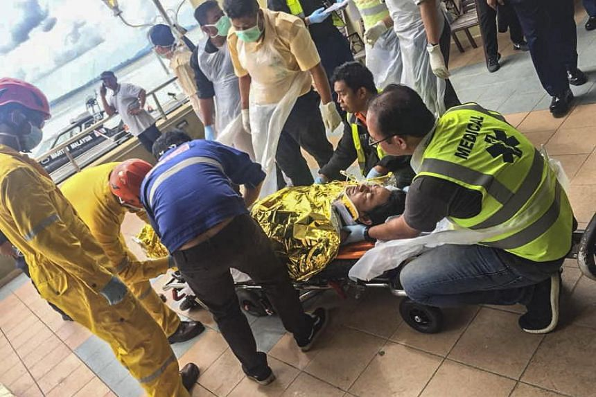 Rescuers help one of the victims of the sinking, on July 2, 2018, in Johor, Malaysia.