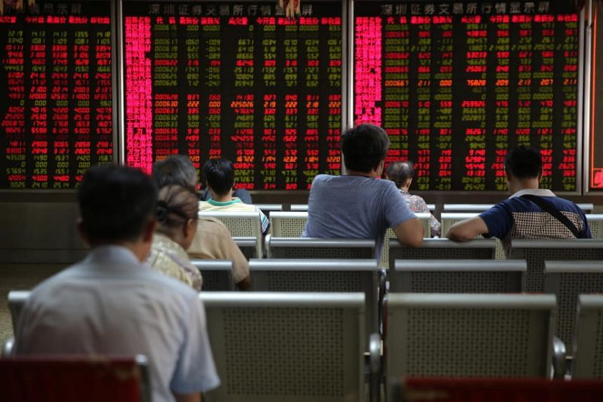 Chinese investors watching an electronic board showing the stock index and prices at a securities brokerage house in Beijing on June 26, 2018.