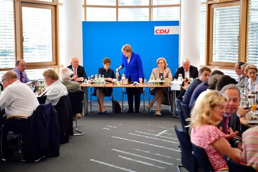 German Chancellor and leader of the Christian Democratic Union (CDU) Angela Merkel (centre) serves coffee to CDU Secretary General Annegret Kramp-Karrenbauer at the beginning of a party leadership meeting at the CDU headquarters in Berlin on July 2,