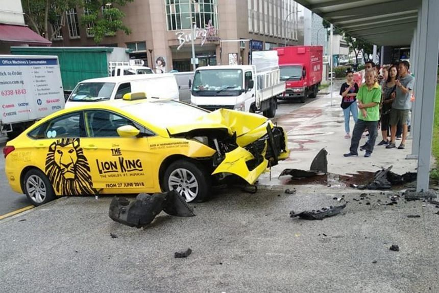 """Facebook user Richard Toh said the taxi had """"shot out"""" of the Sim Lim Square carpark, hitting a van along the way and injuring a pedestrian under a covered walkway."""