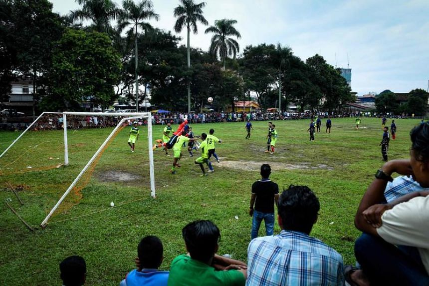 Rohingya residents watching Rohingya FC and Cheras Harimau teams play during a three-day tournament for refugees in Kuala Lumpur on June 17, 2018.