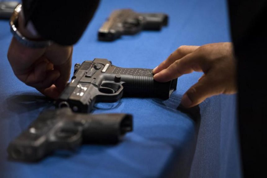 A member of the NYPD lays out guns recovered by police during a press conference about gang violence at New York City Police Department headquarters, on June 27, 2018.