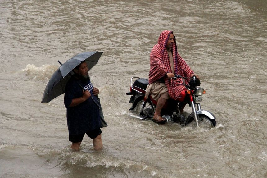 People make their way through floodwaters during heavy rain in Lahore.