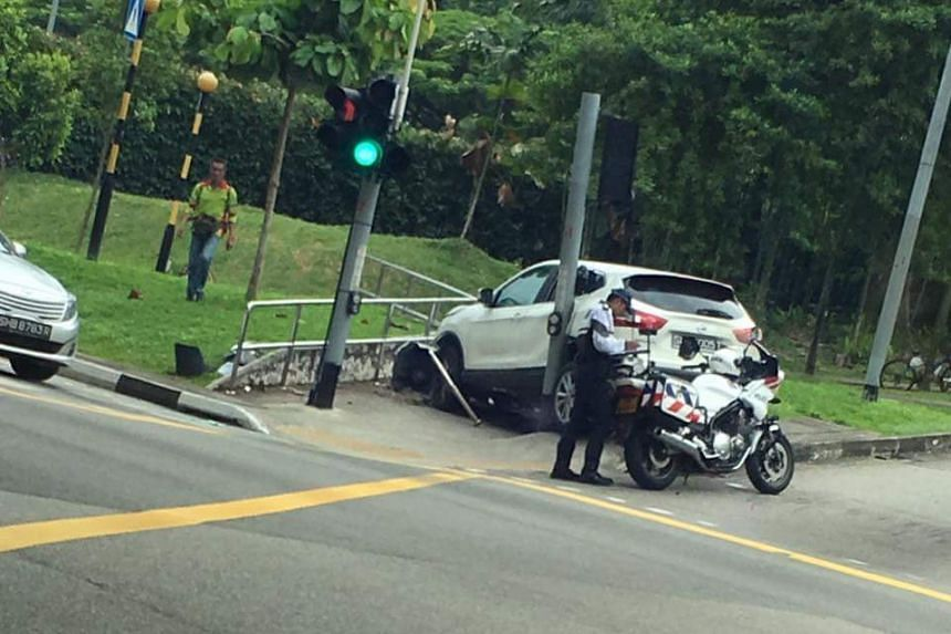 The car, which has a smashed bonnet, appears to have damaged a traffic light and a railing during the accident.