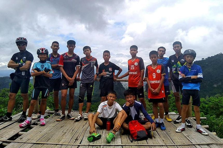 """Members of Thailand's Navy Seals celebrating near the Tham Luang cave complex yesterday after the """"Wild Boars"""" football team members (right, in a group photo recently) were found alive."""