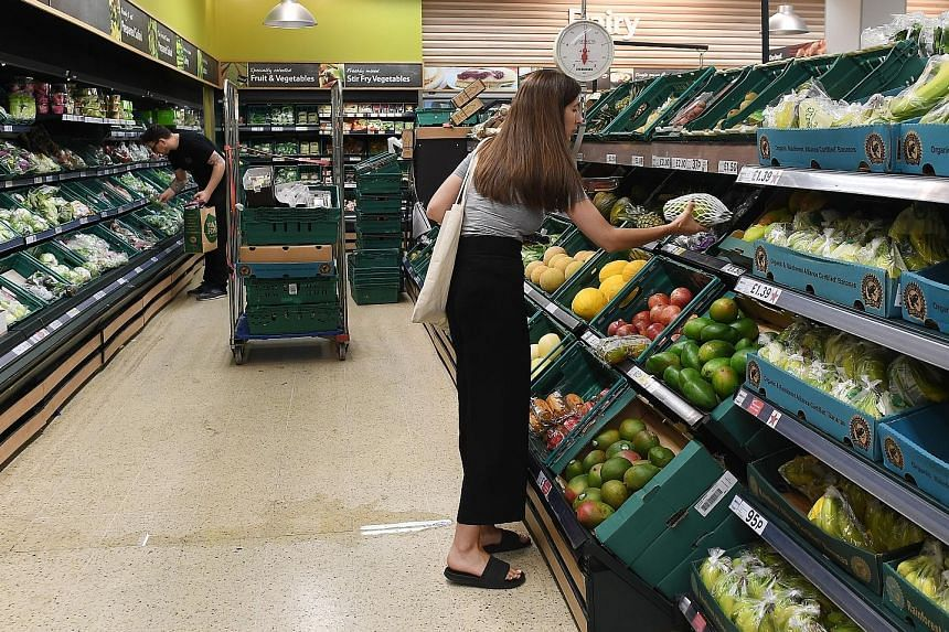 Shoppers at a Tesco supermarket in London. Tesco faces a threat to its market leadership in Britain after second-ranked Sainsbury's agreed to buy Walmart-owned Asda, the No.3 player.