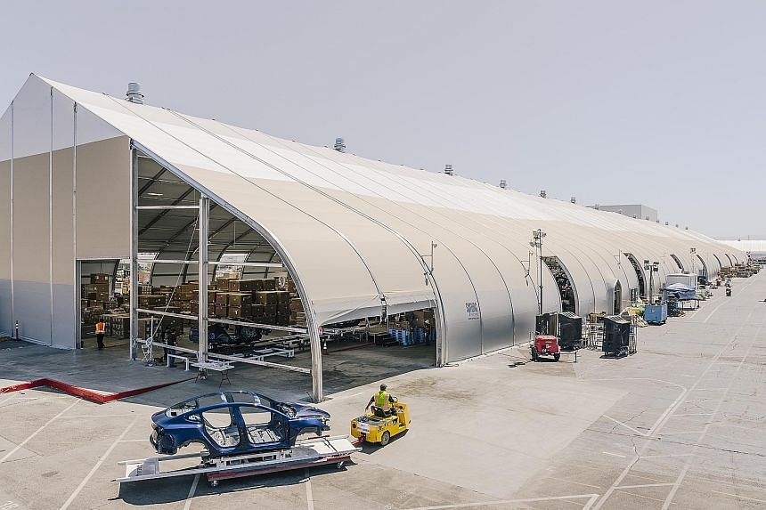 The Model 3 assembly line under a tent at the Tesla factory in Fremont, California, last month. Hitting the target of building 5,000 Model 3 vehicles a week is another against-all-odds achievement for Tesla CEO Elon Musk, who wrote that the company m
