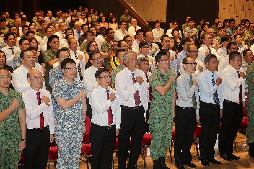 Defence Minister Ng Eng Hen (centre), flanked by Chief of Defence Force Lieutenant-General Melvyn Ong and SCCCI president Roland Ng, reciting the SAF Pledge with representatives from over 100 companies at Jurong Town Hall yesterday.